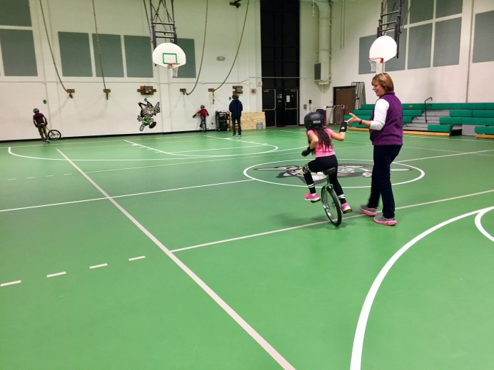 Beech Street School Unicycle C;ub coach Melanie Huberty lends a hand to novice rider Nataly Vazquez.