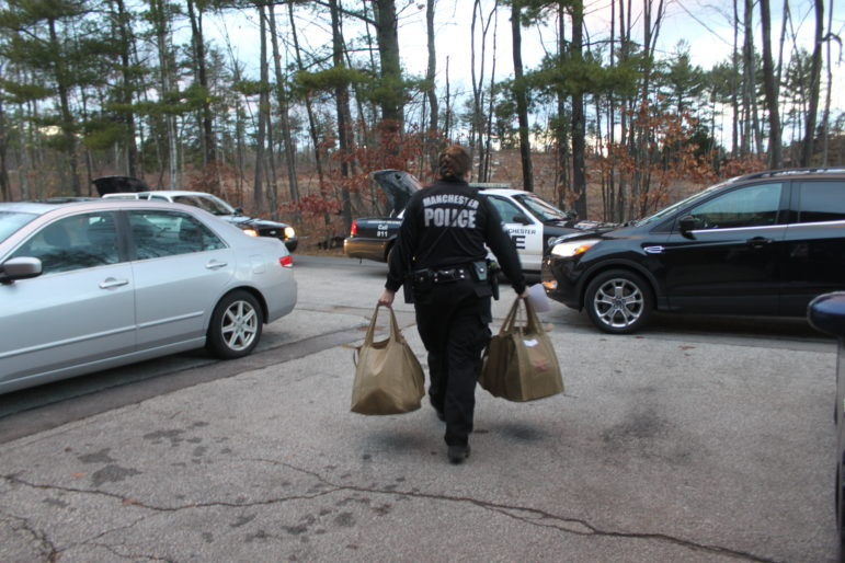 Manchester Police Officer Kelly McKenney carries bags of canned goods ready for delivery to a CareGivers client.