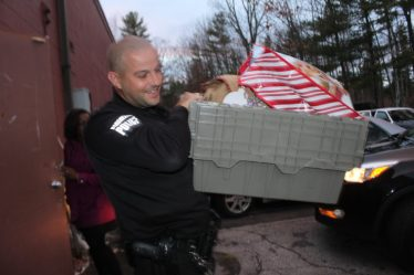 Officer Brian Karoul carries an armload of goodies to his cruiser, ready for delivery.