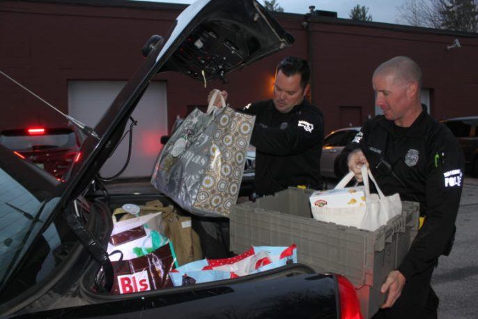 Officer Patrick Mullen, left, and Officer Justin Maguire load the trunk of their cruiser.
