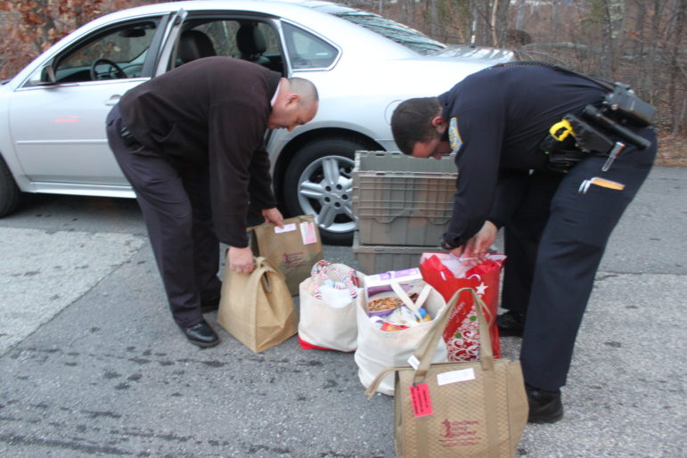 Nashua Police Capt. Jay Maloney, left, and Officer Brandon Cali, go over the goods before heading out for deliveries in Nashua.
