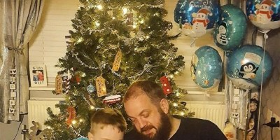 Boy and Dad reading under the christmas tree