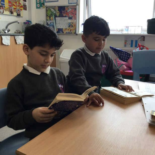 Two children reading books at the table
