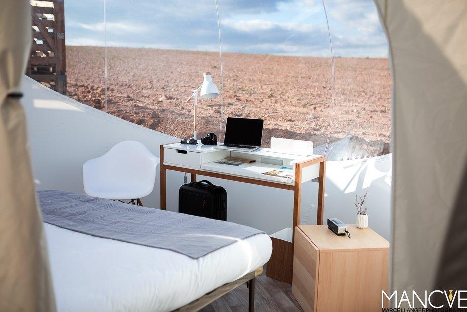 Hotel Aire de Bardenas Bubble Home Wohnzimmer Schreibtisch Bett Wüste Panorama Fenster Macbook Minimalistisch Holz weiß modern