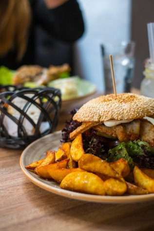 Café Restaurant Katz Kopenhagen Pulled Pork Sandwich Burger Wedges Fries Kartoffelecken Salat Frau Teller Bacon
