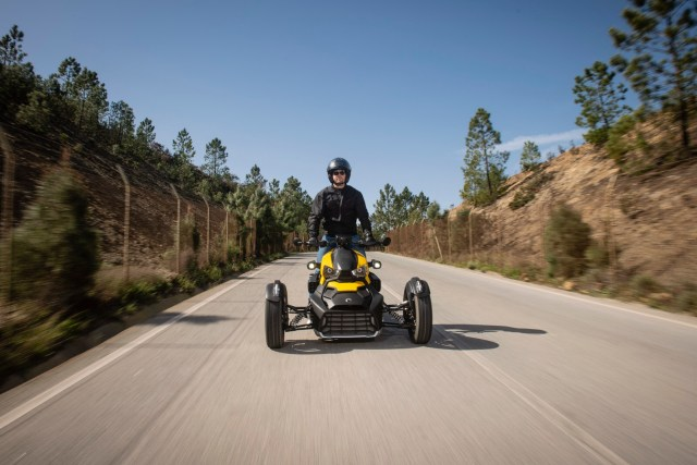 Driver standing on his three wheeler Can-Am Ryker in yellow