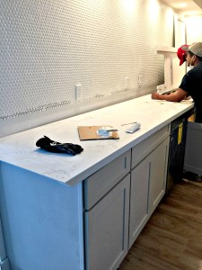 Installation of the new quartz counter tops with a simple and fresh white penny tile backsplash - GORG!