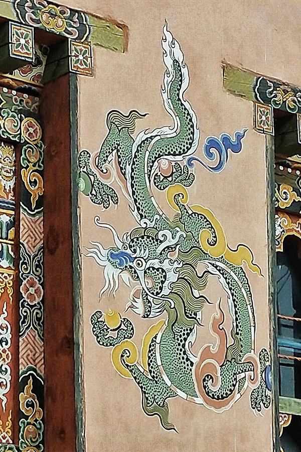 Bhutanese arts and craftsm - Intricate dragon painted onthe side of a building in Bhutan