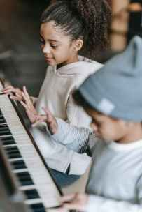 concentrated little black musicians playing piano together at home