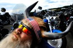 Bearded man with horned helmet looking skyward, in front of motorcycles