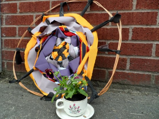 Giant woven pansy and pansy planted in a tea cup