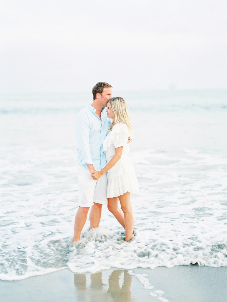 Couple in light blue shirt and white dress on beach in Coronado | Hotel Del Coronado Family Photos | shot on film by Mandy Ford Photography