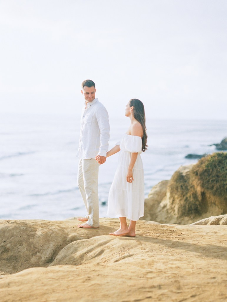Couple walking on Sunset Cliffs during engagement session in San Diego