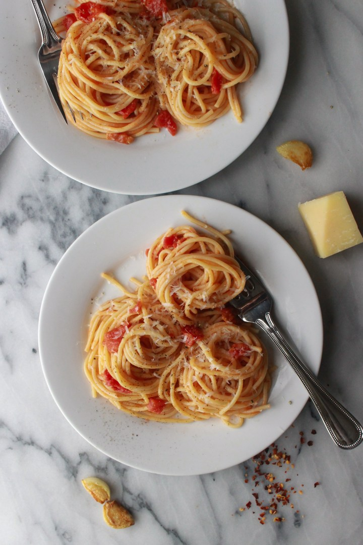 plated spaghetti amatriciana topped with parmesan and black pepper
