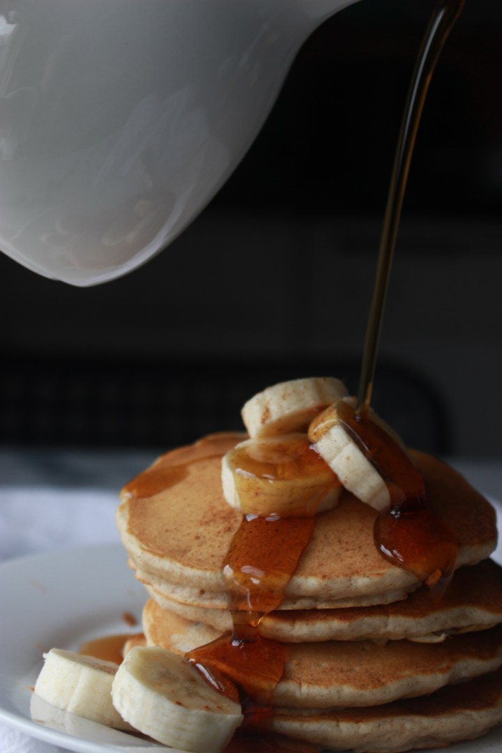 pouring maple syrup all over banana pancakes