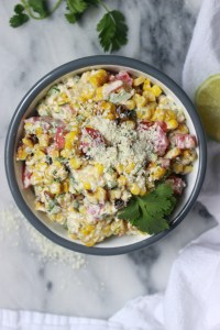 bowl of mexican street corn salad topped with crumbled cotija cheese
