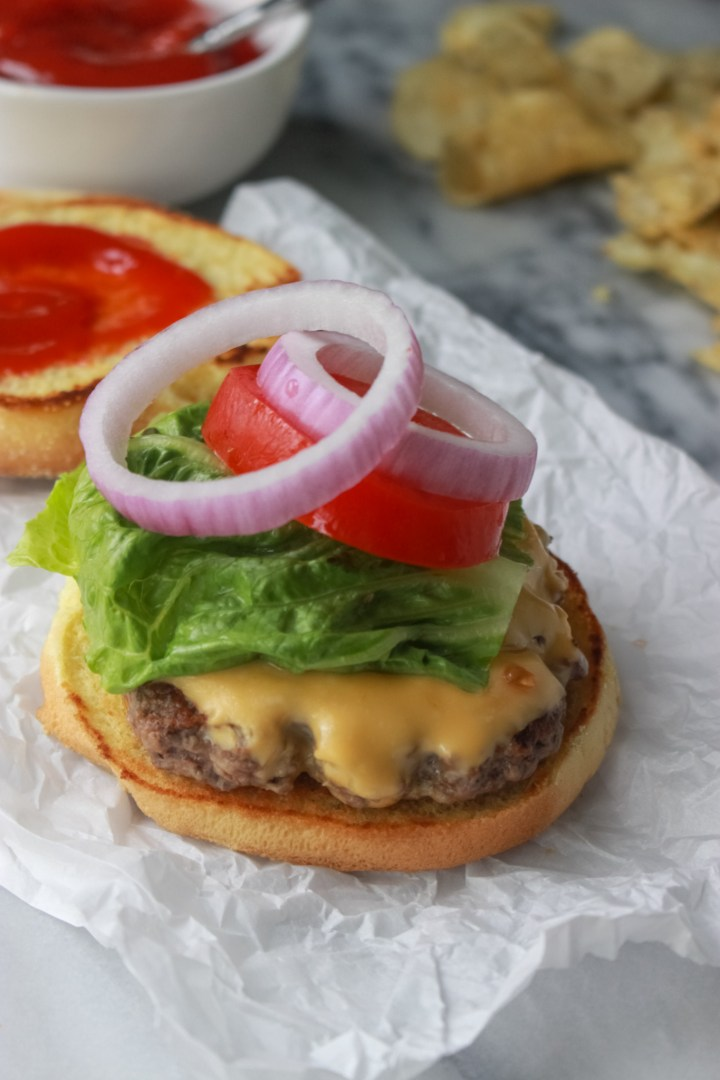 smash burger topped with lettuce, onion, and tomato
