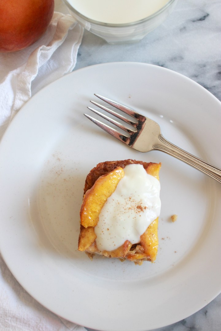 baked oatmeal square topped with peaches yogurt and cinnamon