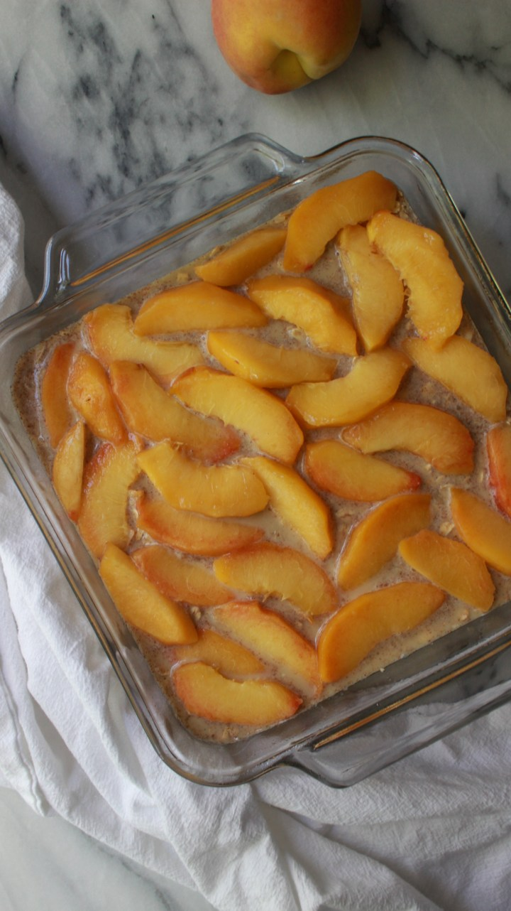 baked oatmeal topped with peaches in baking dish