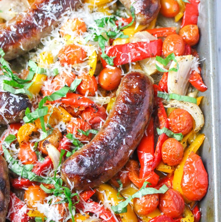 roasted sausage and peppers on sheet pan topped with basil and parmesan cheese