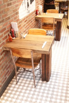 Restaurant two-person tables with seats (one leg), all made from reclaimed woods.