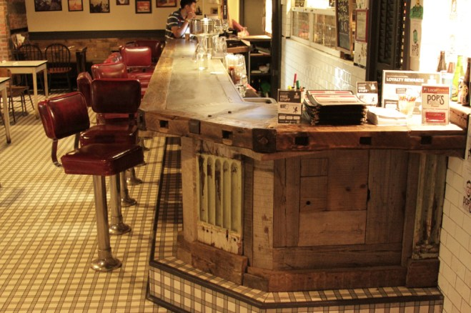Bar counter, top of angled corner. Salvaged column and woods, wrought iron, and artisan's concrete.
