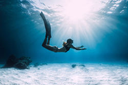 stock-photo-woman-freediver-over-sandy-sea-with-fins-freediving-in-ocean-1382104253