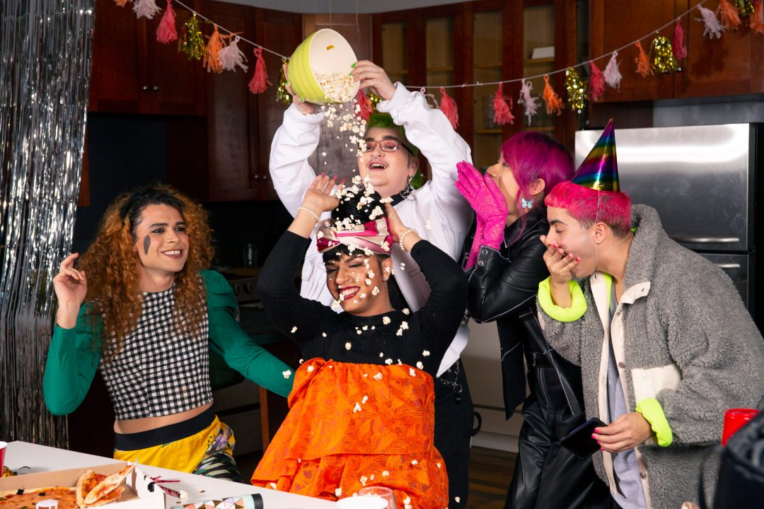 A group of friends of varying genders playing with popcorn at a party