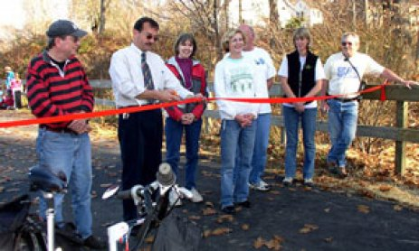 Mayor Mike Tautznik, flanked by members of the Manhan Rail Trail Committee, cuts the ribbon to celebrate the re-opening the washed-out section of trail Nov. 8, 2009.