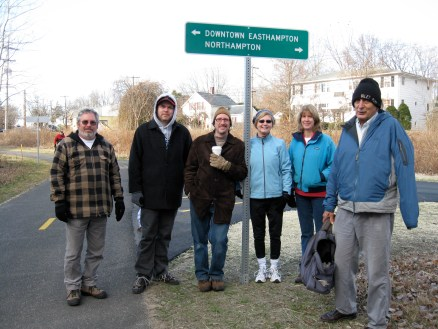 Manhan Rail Trail Committee members Peter Brooks, Mike Chevrette, John Losito, Carla Katz, Barbara LaBombard and Bill Burkart pose in front of the new sign at the fork in the trail near Ferry St. Easthampton.