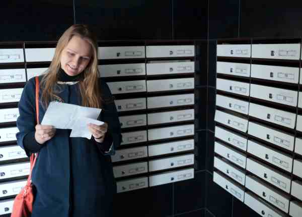 Happy woman reading received letter standing among mailboxes