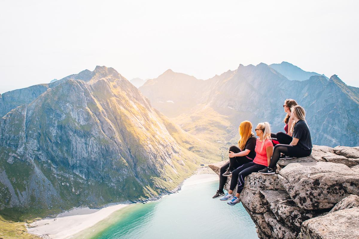 Four girls enjoying the view of Kvalvika Beach from the Ryten cliff