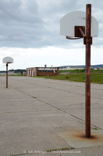 Close-up of two rusty basketball hoops with the Tip-Top garage in the distance. Stephenville, Newfoundland.