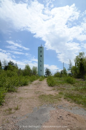 A skinny water tower with the name of the town of Howley, Newfoundland sits under an open sky.