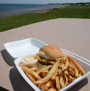 a burger platter on a bench overlooing the beach