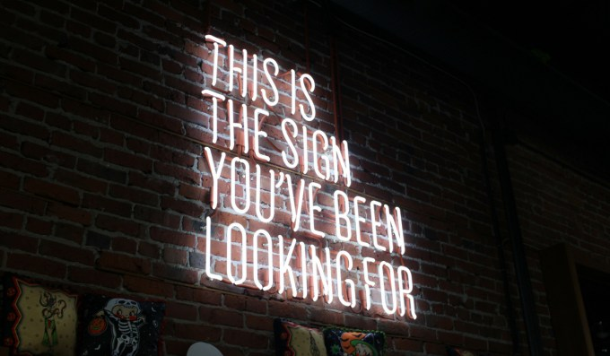 Neon sign: This is the sign that you have been waiting for. Image paired with article titled: manifesting a new money mindset.