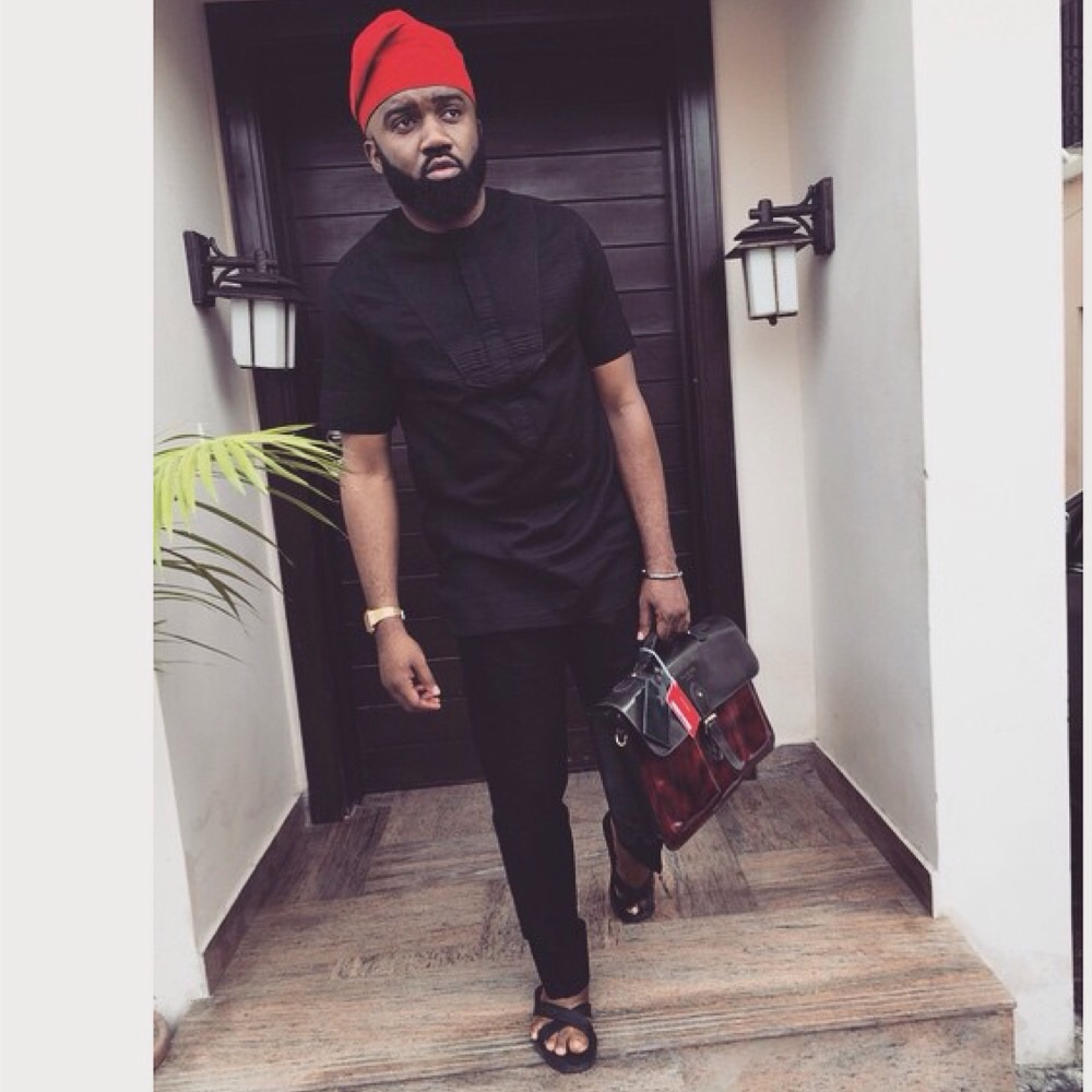 noble igwe in black native wear and red cap