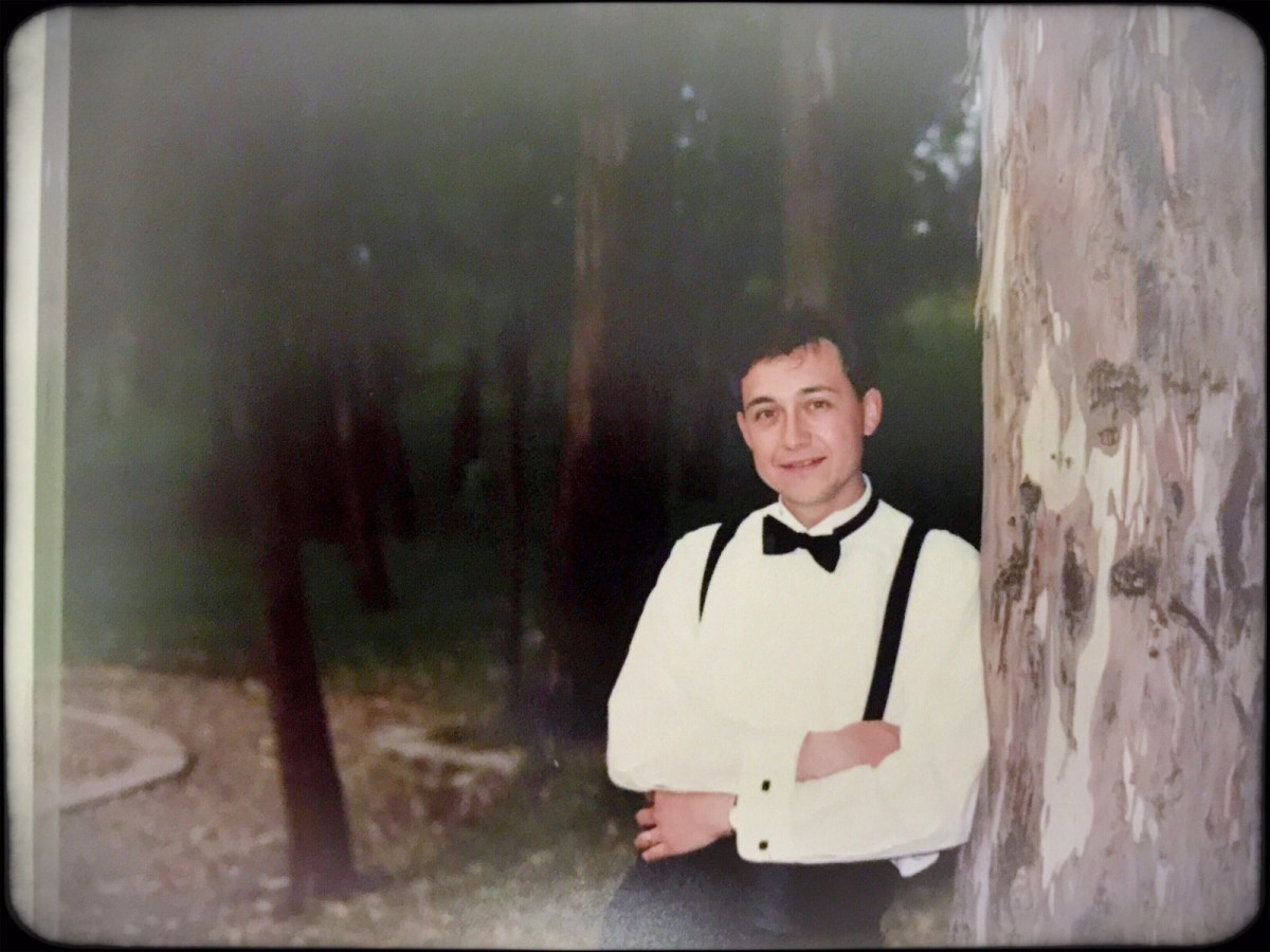 A man of velvet stands next to a tree