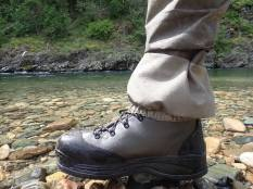 This photo shows the built in gravel guard on the Orvis Silver Sonic Convertible-Top Waders at the edge of a river.