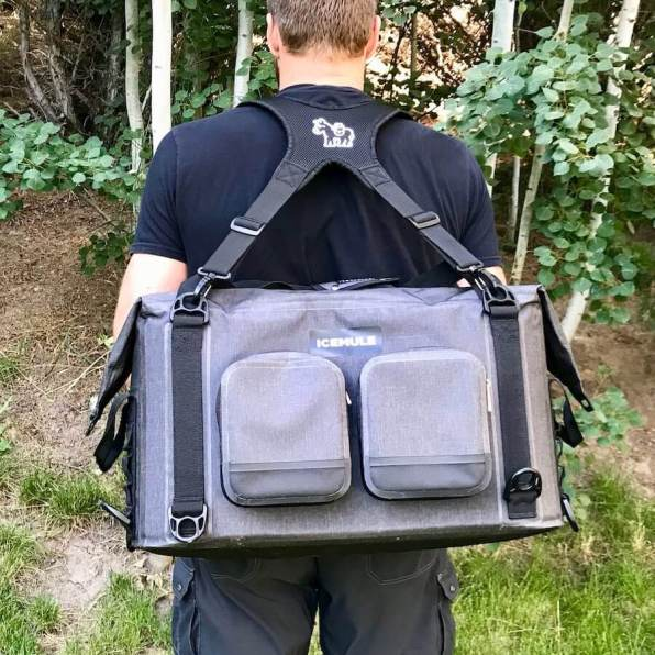 This photo shows a man carrying the ICEMULE Traveler cooler in backpack mode from a rear view.