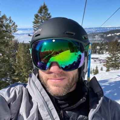 This photo shows the SPY Legacy Goggle being worn by a skier on a ski lift.