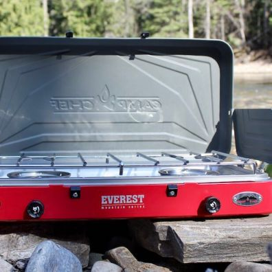 This review photo shows the Camp Chef Everest Two-Burner Camping Stove with the lid and windscreen raised.