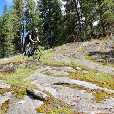 This photo shows the author navigating a gravel bike off-trail on mixed rock and dirt terrain.