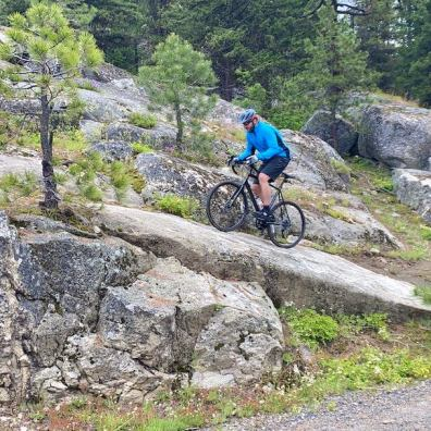 This photo shows the author riding a gravel bike up a slab of granite.