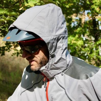 This photo shows the author wearing the Showers Pass Elements mountain biking rain jacket with the hood up.
