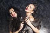 Nightlife. Young happy fashion women celebrating the event in nightclub. Congrats!