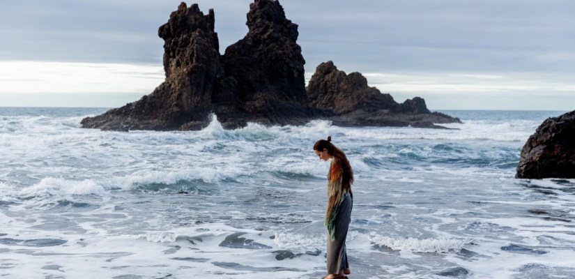 Lonely woman on rocky beach