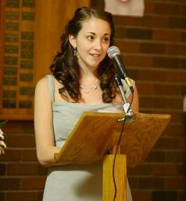 Young woman speaking behind a small lectern