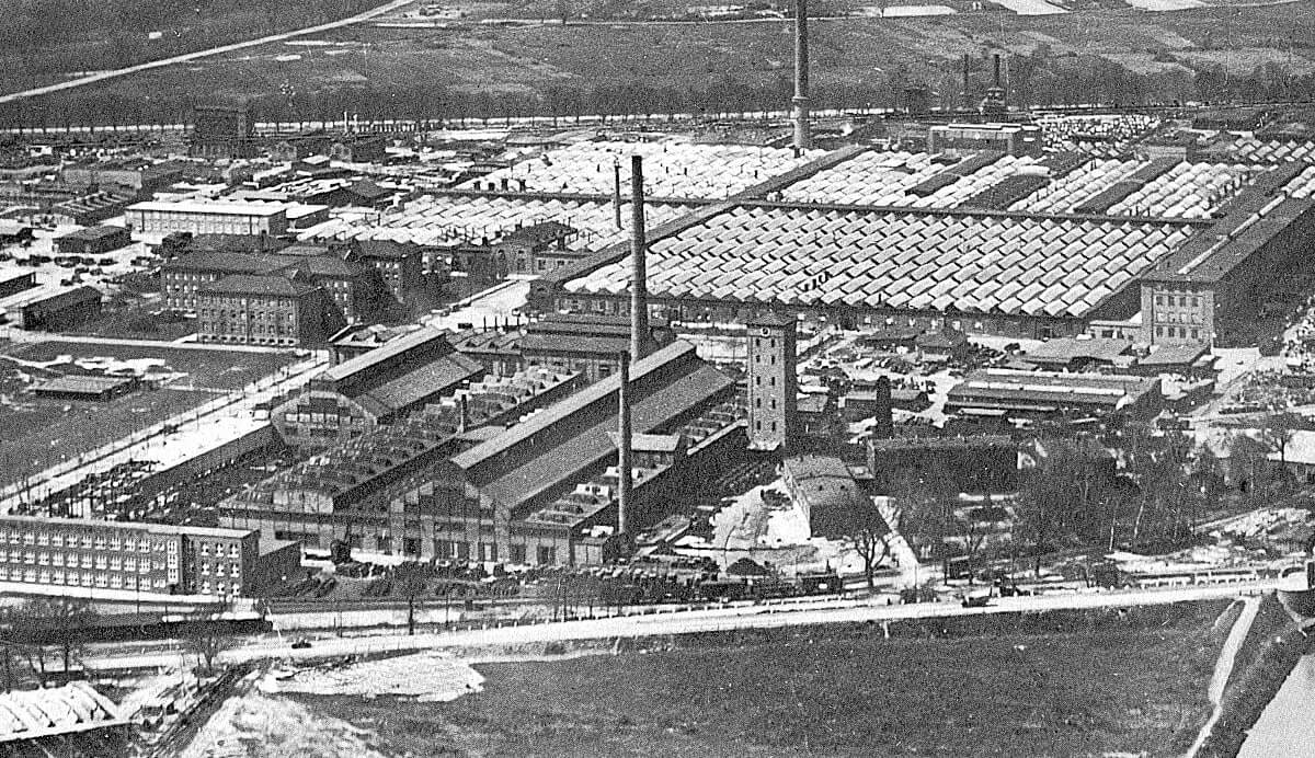 Mann mit Hut Touren: Luftbild von Siemensstadt, Gartenfeld. Etwa 1922. Der Spielort zieht sich vom Turm über das gesamte, überdachte Areal links daneben.
