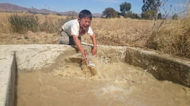 Kid in Jusku Molle checking out the pump that distributes the irrigation water from the reservoir to the fields.